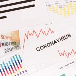 Inscription coronavirus, euro and downward graphs representing financial crisis caused by Covid-19